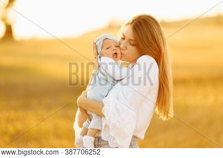 Adorable Mother With Beautiful Little Daughter At The Field, Pretty Woman Hold Cute Newborn Baby In