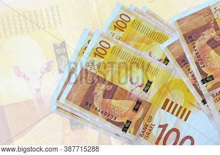 100 Israeli New Shekels Bills Lies In Stack On Background Of Big Semi-transparent Banknote. Abstract