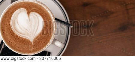 Close Up Coffee Cup With Latte Art Milk Foam On Wood Table, Top View. The Concept Of Relaxing And Ta