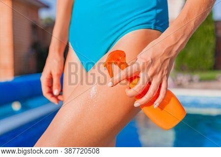 Orange Bottle Of Sun Protection Body Suntan Lotion, Moisturizing Sunblock In Female Hand. Skin Body