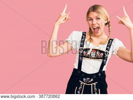 Young beautiful blonde woman wearing oktoberfest dress shouting with crazy expression doing rock symbol with hands up. music star. heavy music concept.