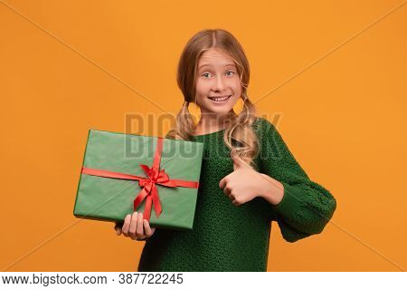 Charming Blonde Girl 12-14 Years Old In Warm Green Sweater Shows Thumb Up With A Present Box In Her