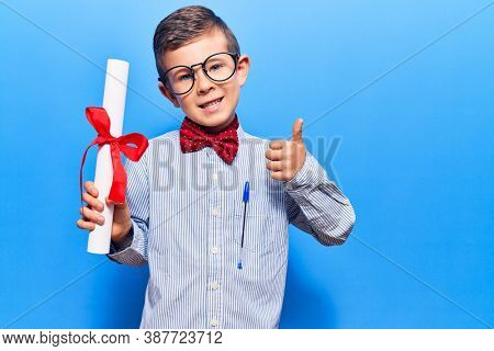 Cute blond kid wearing nerd bow tie and glasses holding diploma smiling happy and positive, thumb up doing excellent and approval sign
