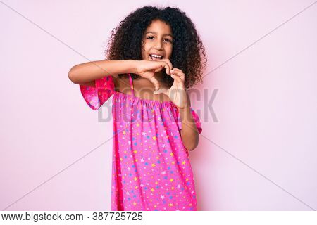 African american child with curly hair wearing casual dress smiling in love doing heart symbol shape with hands. romantic concept.