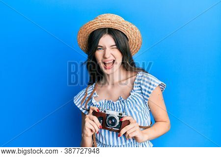 Young beautiful caucasian girl holding vintage camera winking looking at the camera with sexy expression, cheerful and happy face.