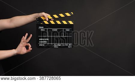 Hands Is Holding Clapper Board Or Movie Slate.it Is Used In Video Production And Film Industry On Bl