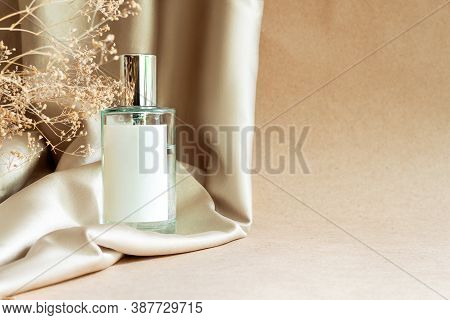 Closeup Glass Bottle Of Aromatic Floral Luxury Perfume On Background Of Beige Fabric Drapery. Cosmet