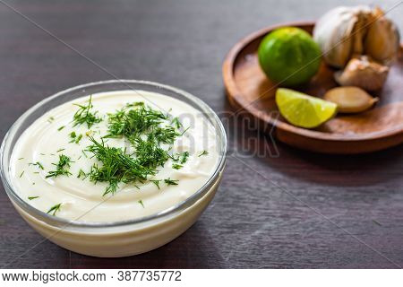 Homemade Vegetarian Mayonnaise Garnished With Dill, In The Background A Wooden Plate With Lime And G