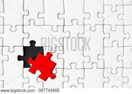 White Gray Puzzles Are Stacked On Black Background. One Piece, Colored Red, Located Separately. Not
