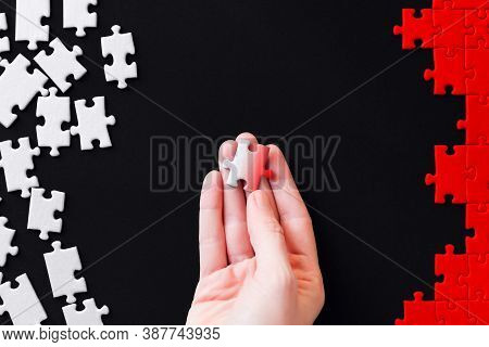 Female Hand Is Holding Piece Colored In Gradient. White Puzzles Are Scattered On Left Side And Red S