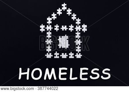 Decorative House Laid Out From White Puzzles On Black Background. Inscription, Text, Word Homeless I