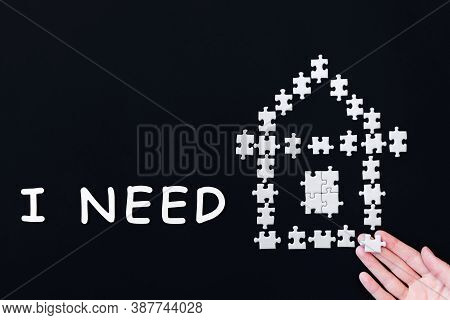 Decorative Paper House Laid Out From White Puzzles On Black Background. Inscription, Text, Words I N