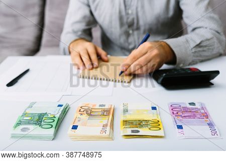 Euro Banknotes Are Stacked. Man Doing His Accounting. Distribution Of Expenses In A Small Business.