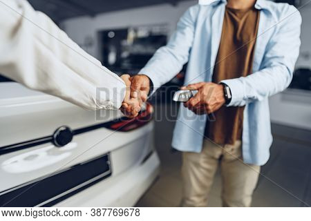 Car Seller And Buyer Handshake At Car Dealership Against A New Car