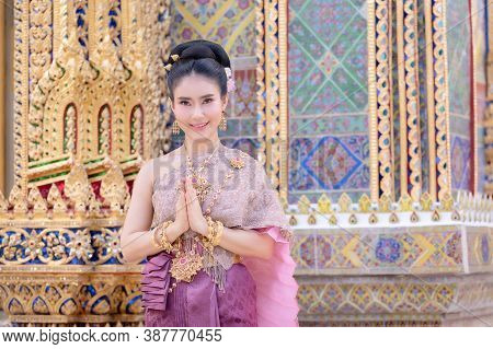 A Beautiful, Graceful Thai Woman In Thai Dress Adorned With Valuable Jewelry Raise Her Hand To Pay R
