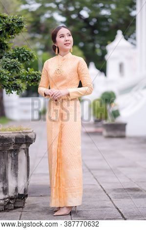 A Beautiful, Graceful Thai Woman In Thai Dress Adorned With Valuable Jewelry Stands In A Beautiful A