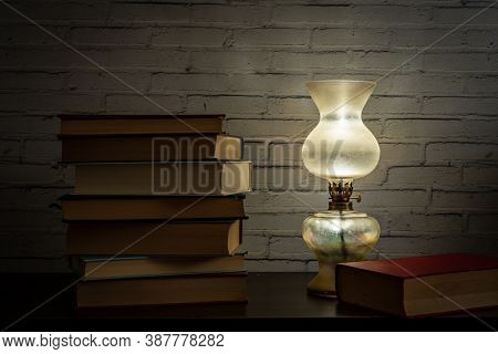 The Light Of An Oil Lamp Illuminates Books Placed On A Dark Wooden Surface, Still Life In Soft Light