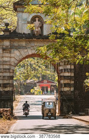 Old Goa, India. Auto Rickshaw Or Tuk-tuk Moving Through The Old Viceroy S Arch. Famous Vasco Da Gama