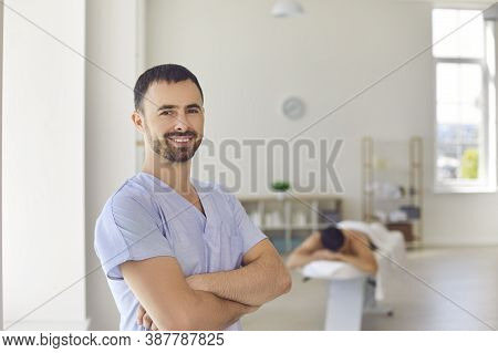 Smiling Masseur Or Physiotherapist Standing Arms Folded In Massage Room Of Modern Health Center