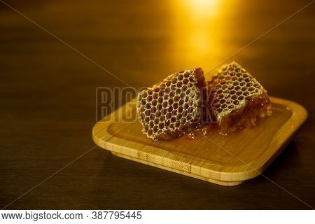 On A Brown Wooden Table, Honeycombs Lie In The Warm Golden Ligh.