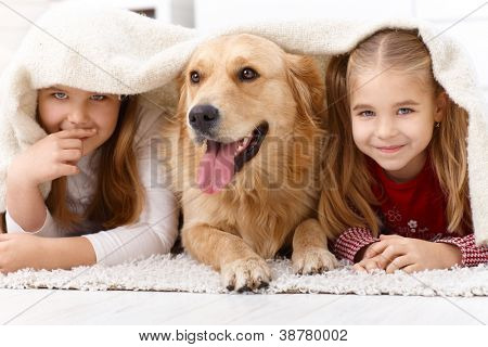 Cute little girls having fun with golden retriever, lying prone on floor at home under blanket, smiling.