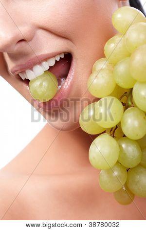 Closeup female lips eating grapes, holding a grape between teeth.