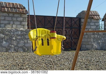 Empty Lonely Swing In Yellow On The Playground. Simple Rides For Relaxation. Outdoor Entertainment.