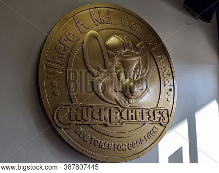 Honolulu - September 15, 2019: Gold Chuck E. Cheese Emblem On Wall.   Large Coin Says .. Where A Kid