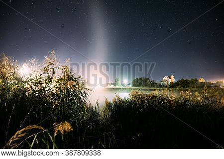 Evaporation Over River Lake Near Houses In Village. Night Starry Sky Above Misty Lake River Landscap