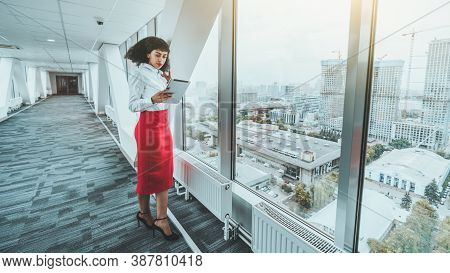 A Beautiful Young African-american Woman Entrepreneur In A White Shirt And Red Skirt Is Reading Work