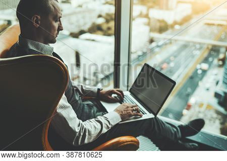 Side View Of A Mature Handsome Caucasian Man Entrepreneur Working On His Netbook While Sitting In A