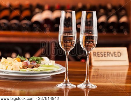 Two Glasses Of Champagne With A Tray Of Cheese And Reserved Message.