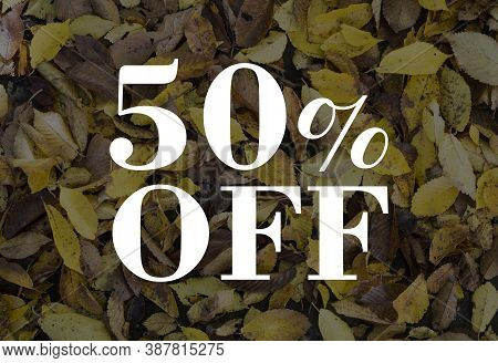 The Inscription 50% Off On A Background Of Yellow And Brown Leaves Fallen From A Tree.