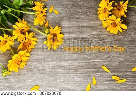 Yellow Daisies And The Inscription Happy Mother's Day On A Wooden Background. Promotional Content Fo