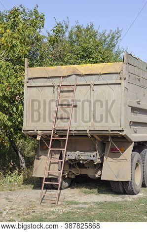 Ladder At The Rear Of A Dump Truck On The Side Of The Road. Truck With High Sides And A Closed Awnin