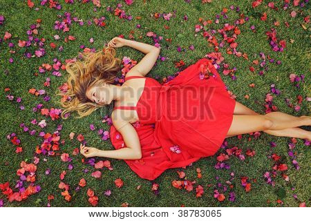 Beautiful Young Woman Lying on Grass with Flowers In Red Dress