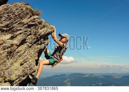 A 11-year-old Boy Is Studying Mountaineering In The Carpathians, A Boy Climbs To The Top Of A Rocky