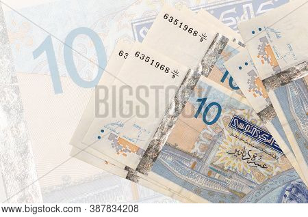10 Tunisian Dinars Bills Lies In Stack On Background Of Big Semi-transparent Banknote. Abstract Pres