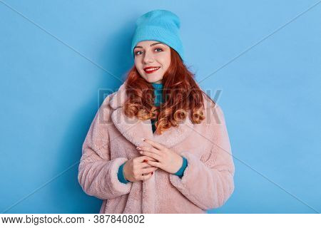 Beautiful Woman Wears Pink Fur Coat And Blue Cap, Smiles Toothily, Wears Red Lipstick, Looks At Came