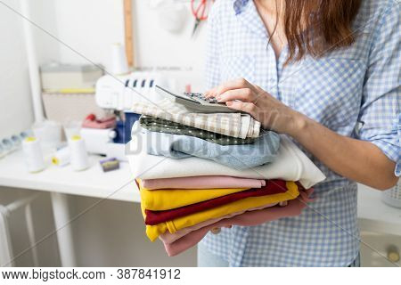 Home-based Business: A Girl Holds A Stack Of Multi-colored Fabrics In Her Hands And Makes Calculatio