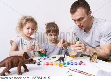 Hobby: Dad With Son And Daughter Paint Small Figures Of Dinosaurs With Paint And A Brush.