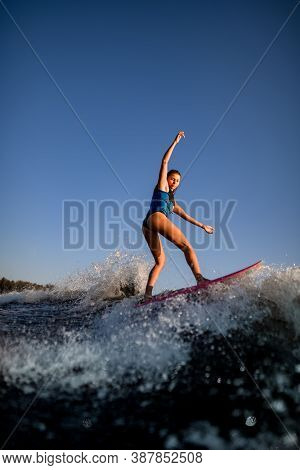 Young Attractive Woman Vigorously Rides The Wave On Surf Style Wakeboard