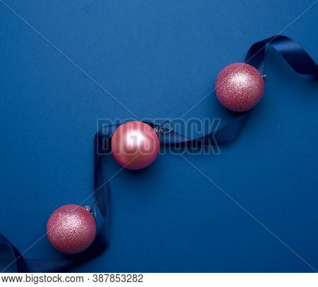 Silk Ribbon And Pink Shiny Christmas Balls On A Blue Background, Festive Backdrop For Christmas And