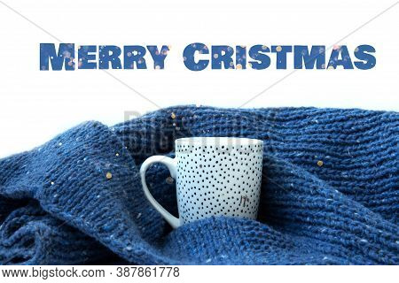 White Ceramic Cup With Gold Dots Wrapped In Warm Blue Knitted Sweater On White Background. Merry Chr
