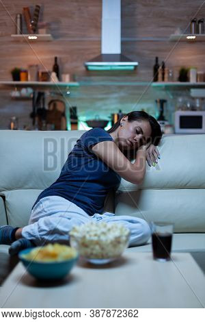 Tired Lonely Woman Sleeping On Sofa In Living Room While Watching Film. Exhausted Sleepy Young Lady