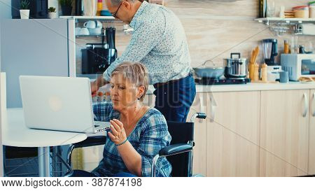 Disabled Old Woman In Wheelchair Working On Laptop In Kitchen. Paralysied Handicapped Old Elderly Pe