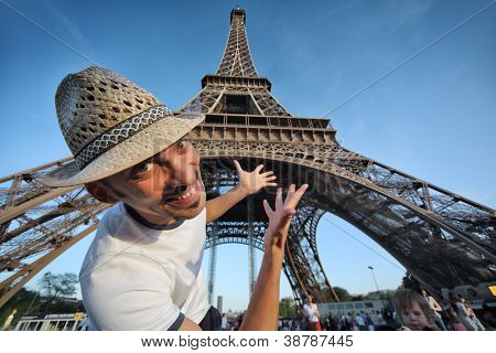 Welcome to Paris! Happy smiling tourist pointing to Eiffel Tower in Paris, France.