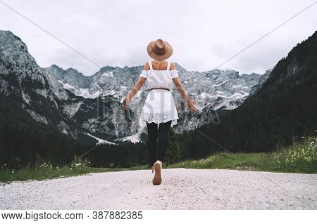 Beautiful Woman Stands On Background Of Mountains.