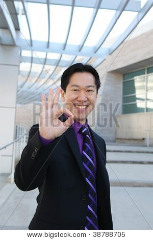 A handsome Chinese business man at office building indicating success (Focus on Hand)