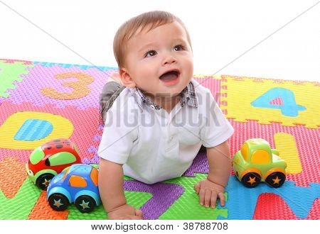 A cute young baby boy playing with his colorful toys